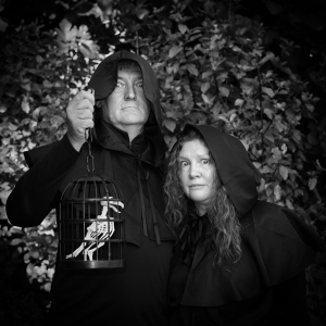 Two hooded figures holding a prop raven